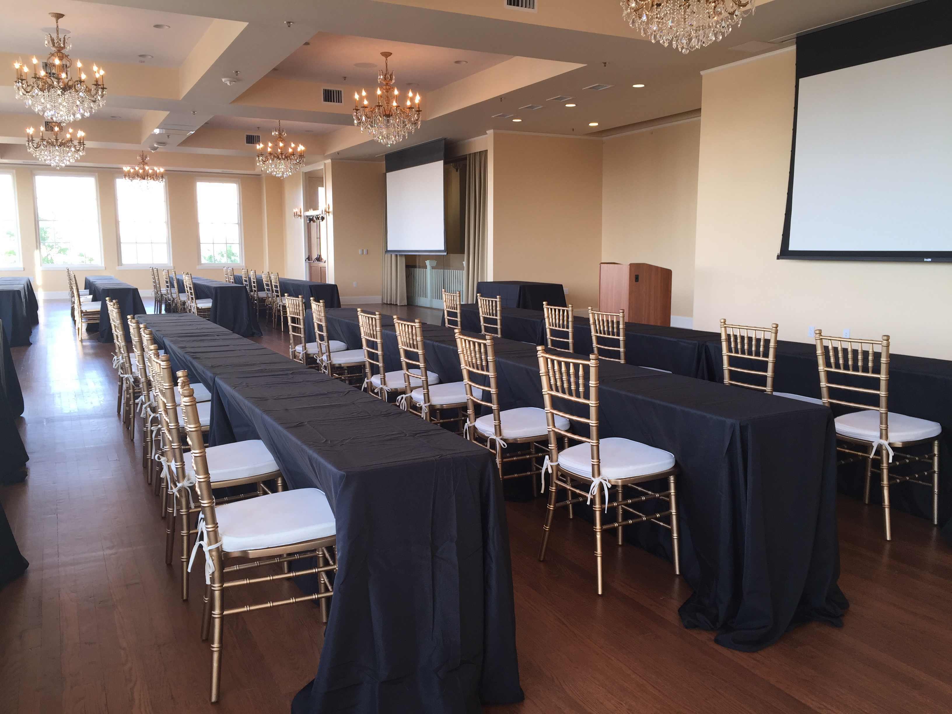 Long classroom tables with black linens face a projection screen at the front of the room.