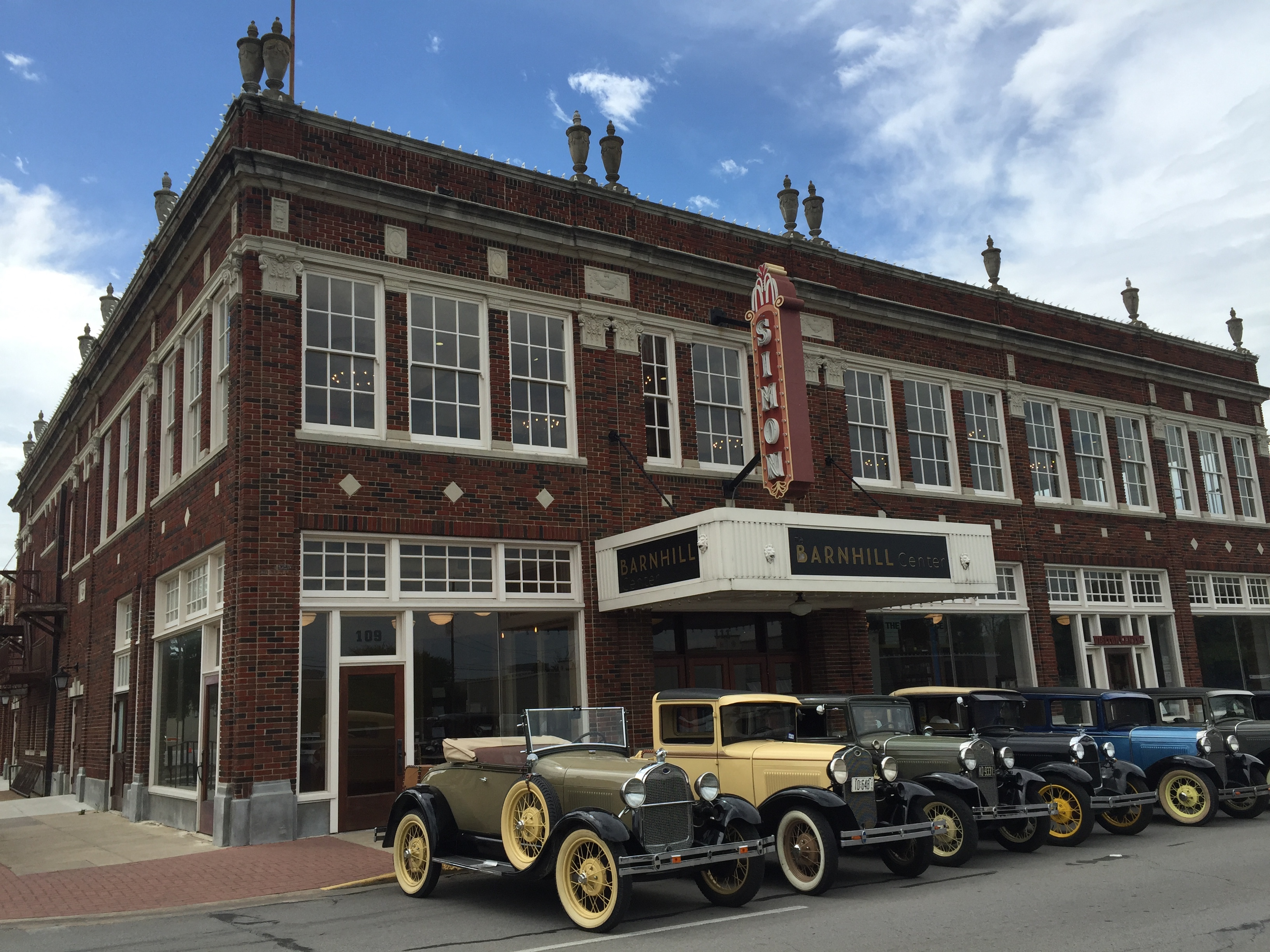 An exterior shot of the Barnhill Center features vintage cars parked in a row.