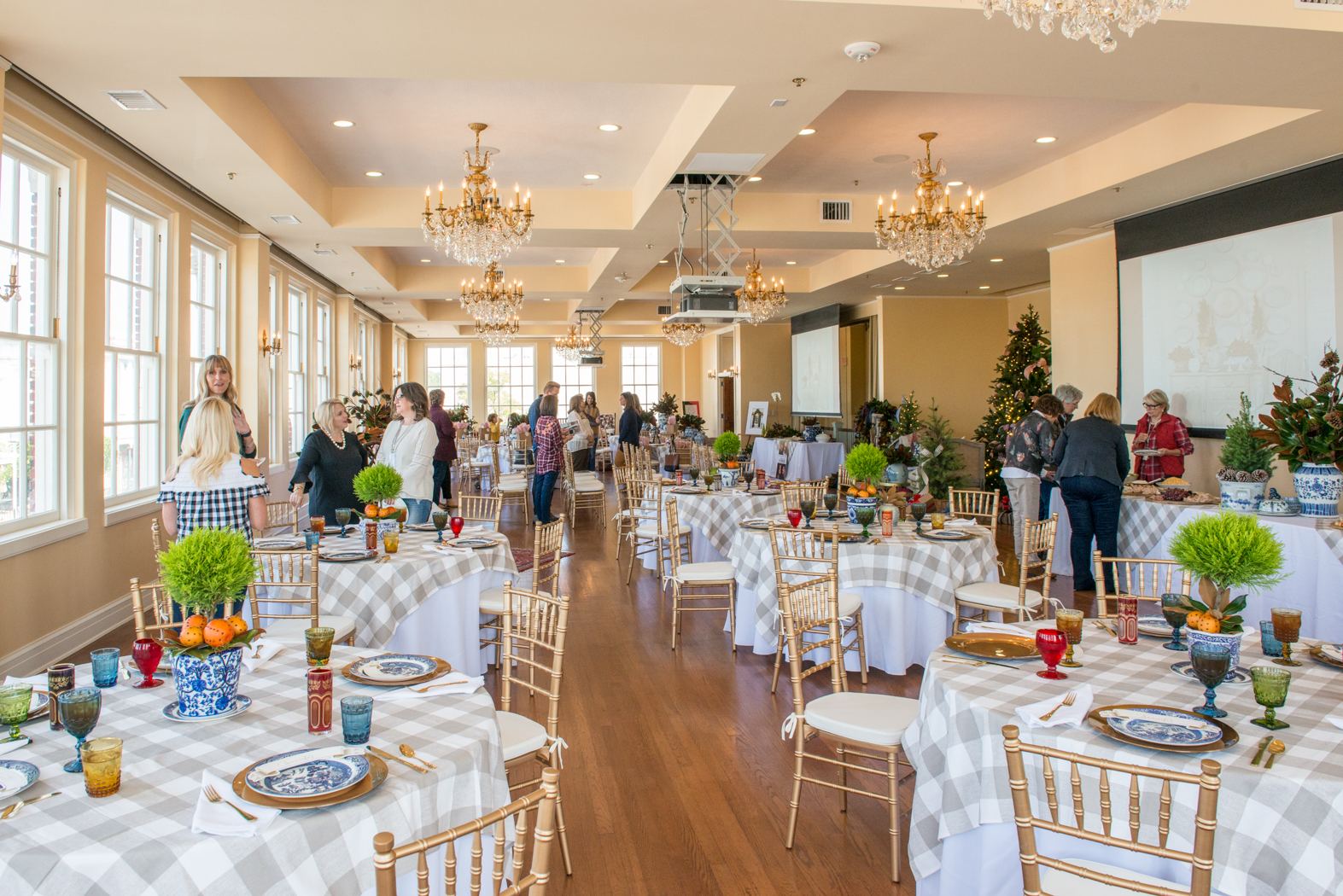 The light-filled Bullock Ballroom is prepared for a classroom event. White and cream checkered linens adorn each table, decorated with gold chargers, blue willow china, green and blue goblets and green topiary centerpieces.