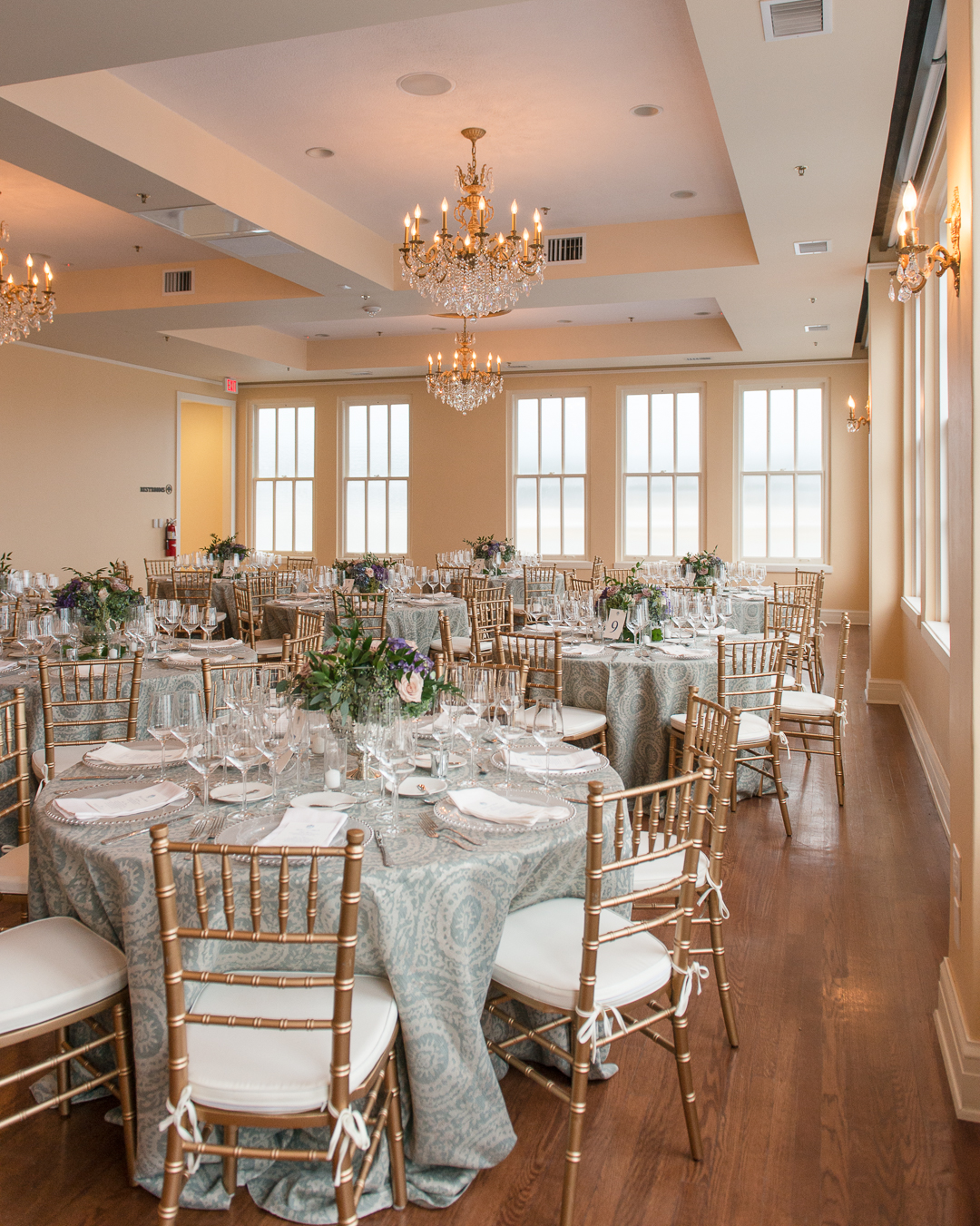 Elegant gold Chiavari chairs surround tables draped in blue and white linens. Tables are set with fine white china and crystal goblets. Centerpieces of hydrangeas, roses, and ferns are placed on each table.