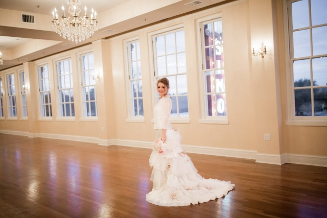 Bride in white dress stands in elegant ballroom with chandeliers, wooden flooring and windows looking out to a sunset.