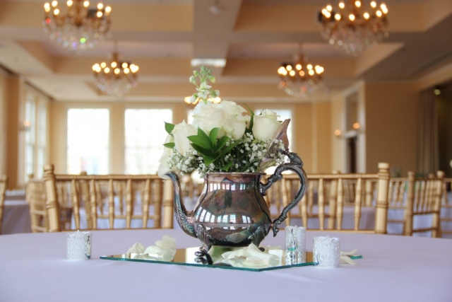 A silver teapot full of white roses and baby's breath sits atop a glass mirror sprinkled with rose petals and silver candles.
