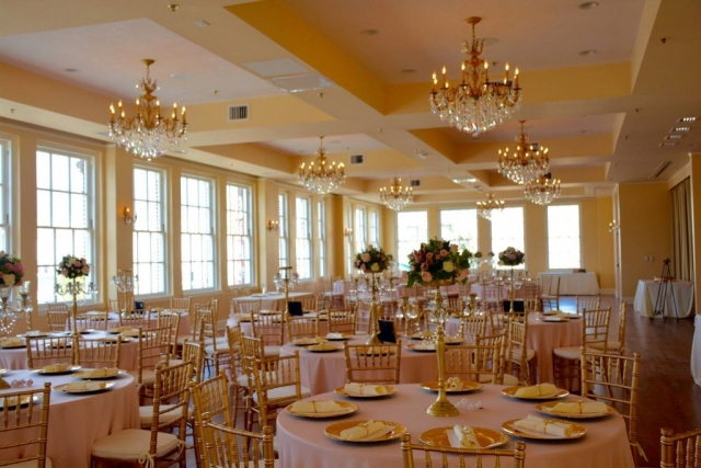 White linen tables with gold charges at each place setting. Tall gold chandeliers topped with rose arrangements.