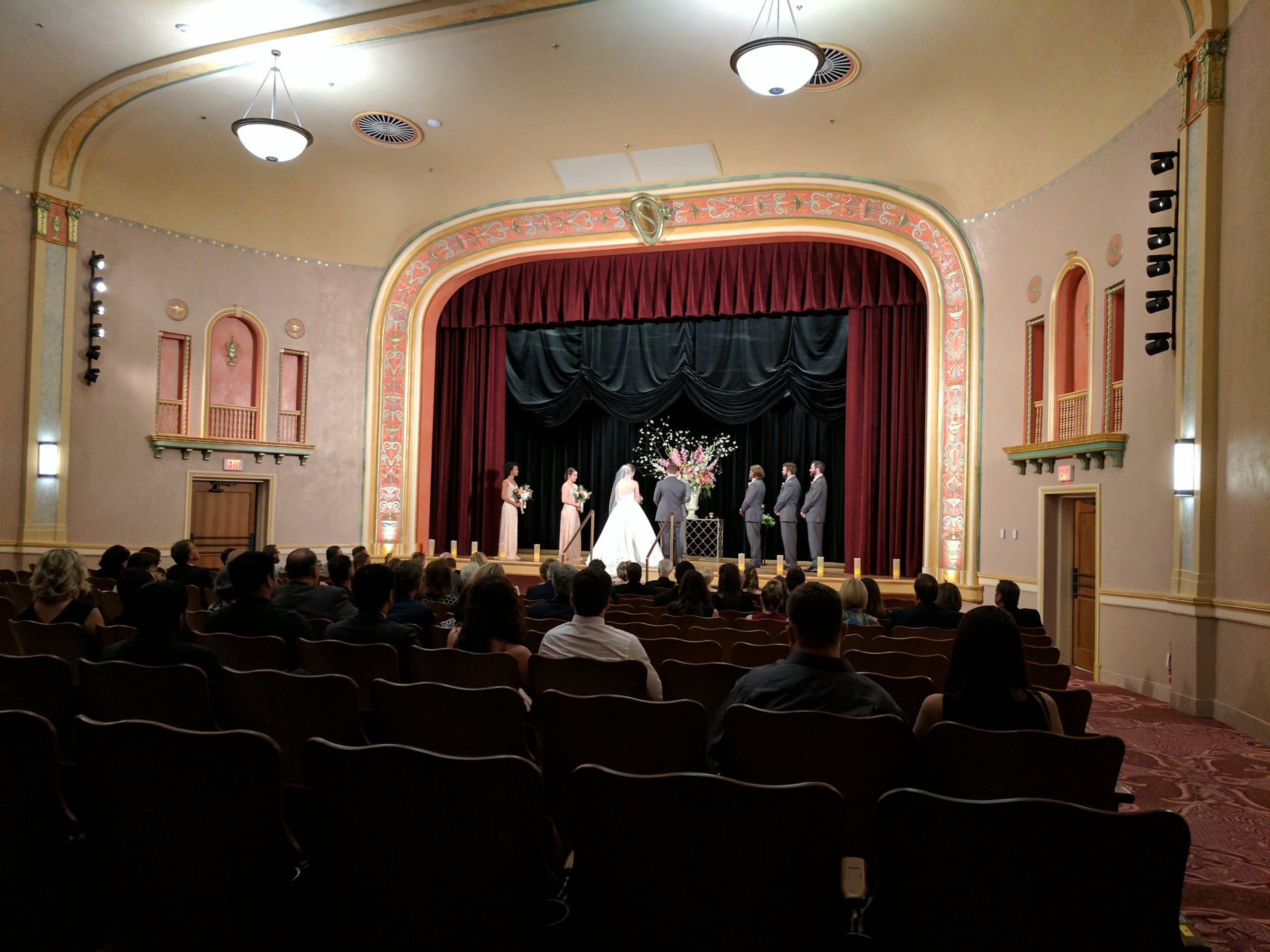 A wedding party stands on the stage of the Hasskarl Auditorium during their wedding ceremony.