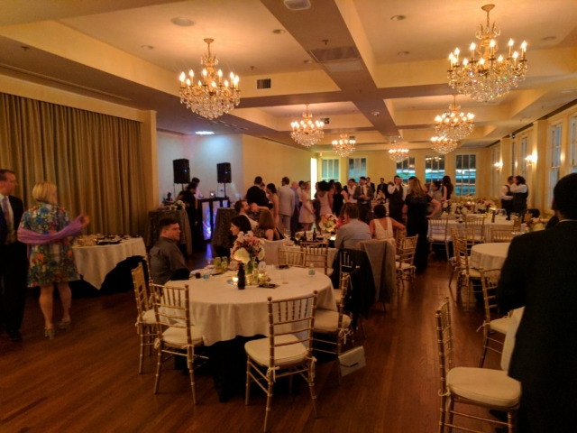 A wedding reception takes place in the Bullock Ballroom as party guest mingle around tables dressed in white linens.