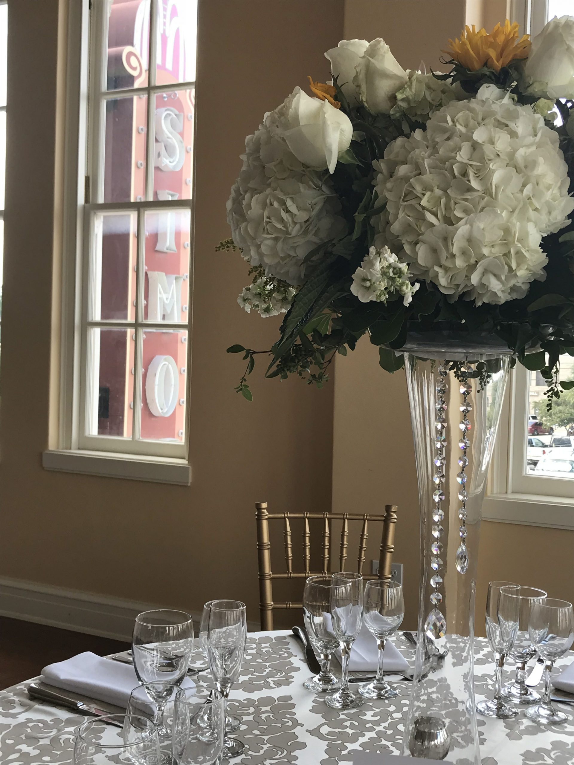 A beautiful, tall crystal vase is topped with an arrangement of white hydrangeas, white roses and yellow sunflowers. Crystal beads hang down from the arrangement. The Simon marquee is seen outside the window.