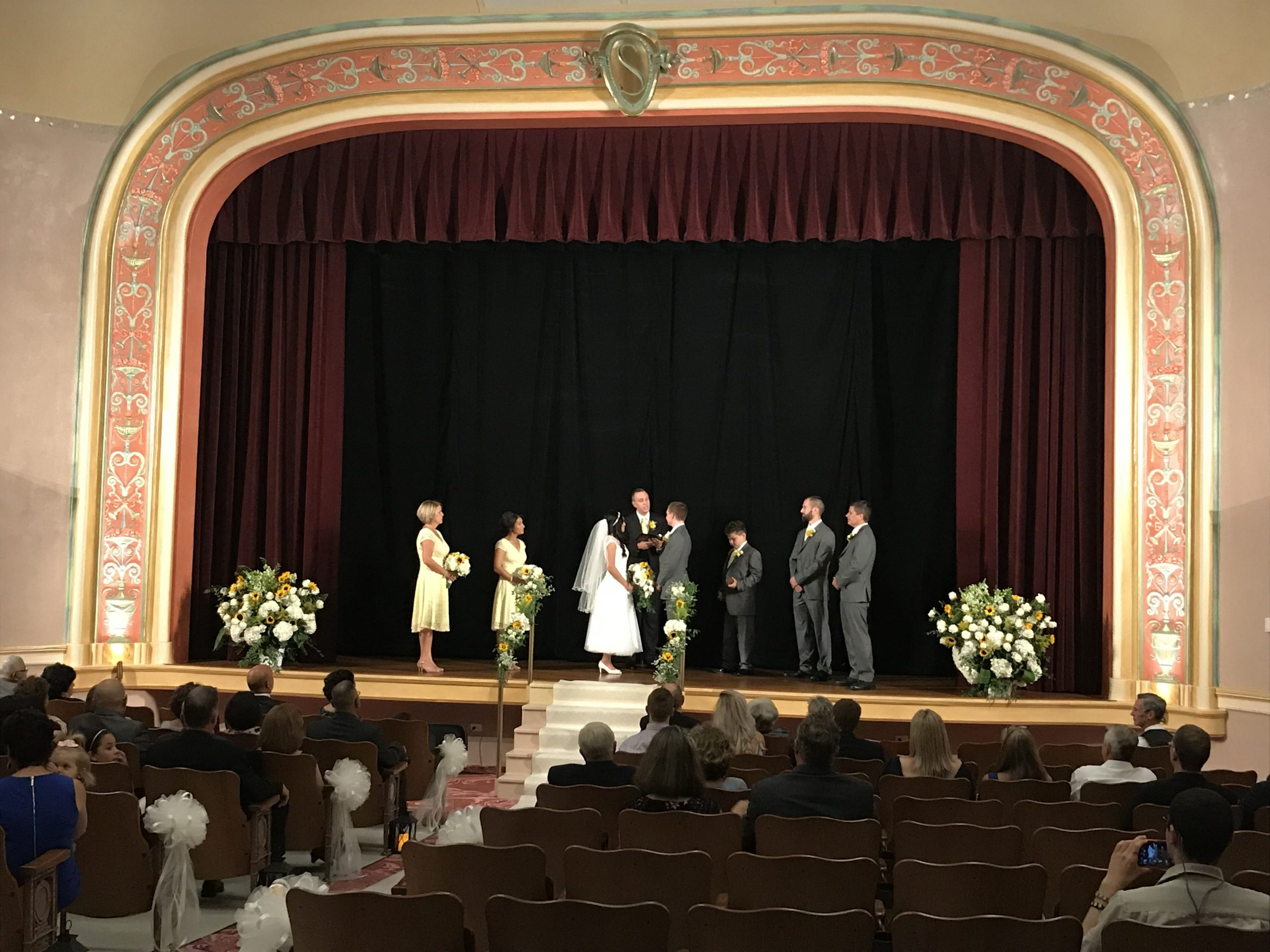 A bride and groom stand on the stage of our vintage Vaudeville theatre with several groomsmen and bridesmaids on either side. The stage is adorn with white flower and yellow sunflowers in large arrangements. Guests look on from the comfort of the theatre's comfy chairs.