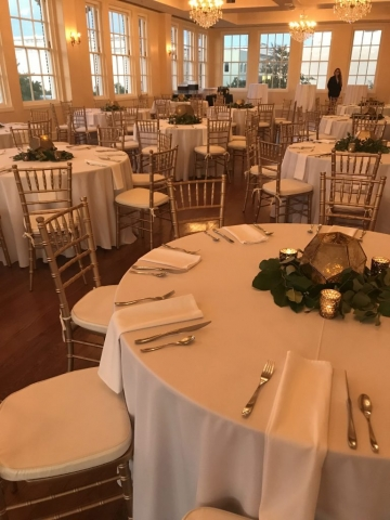 White linen tablecloths cover round tables in the ballroom. Atop each table is a circle of green eucalyptus with golden tea lights throughout. The centerpiece is a rustic, gold geometric orb with a candle in the center.