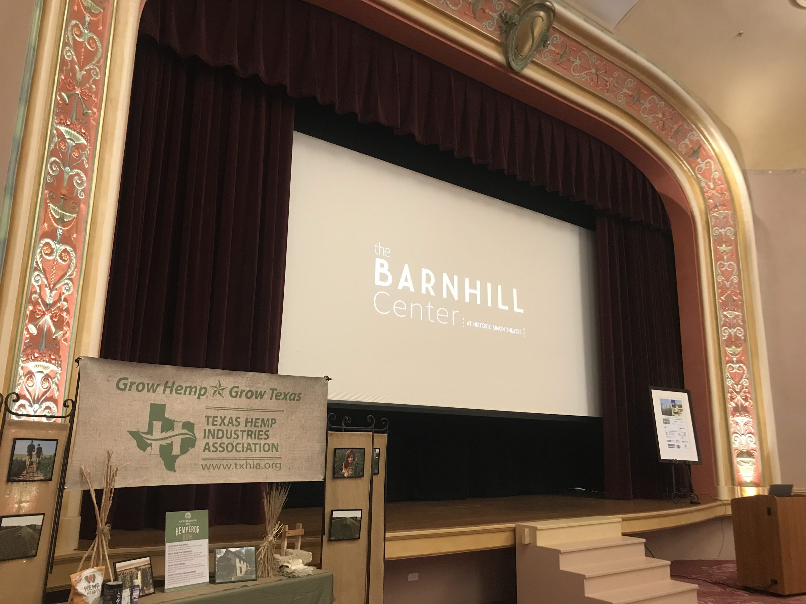 Interior shot of the Hasskarl Auditorium prepared for a multi-day conference. The screen is down showing the Barnhill Center logo with a visible podium and vendor booth in view of the stage.
