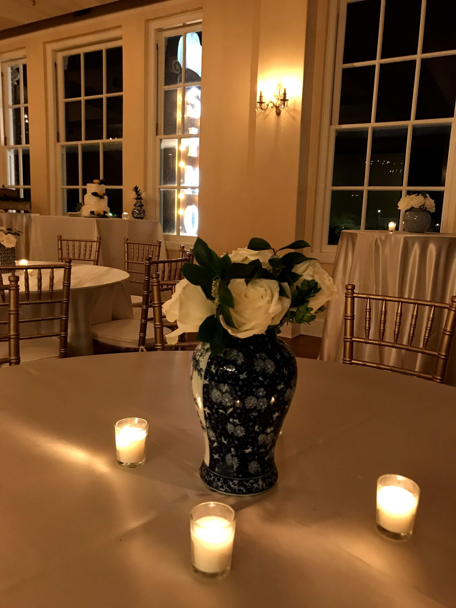 A blue vase centerpiece filled with white flower and surrounded by tea lights. In the background, the Simon marquee twinkles out the window.