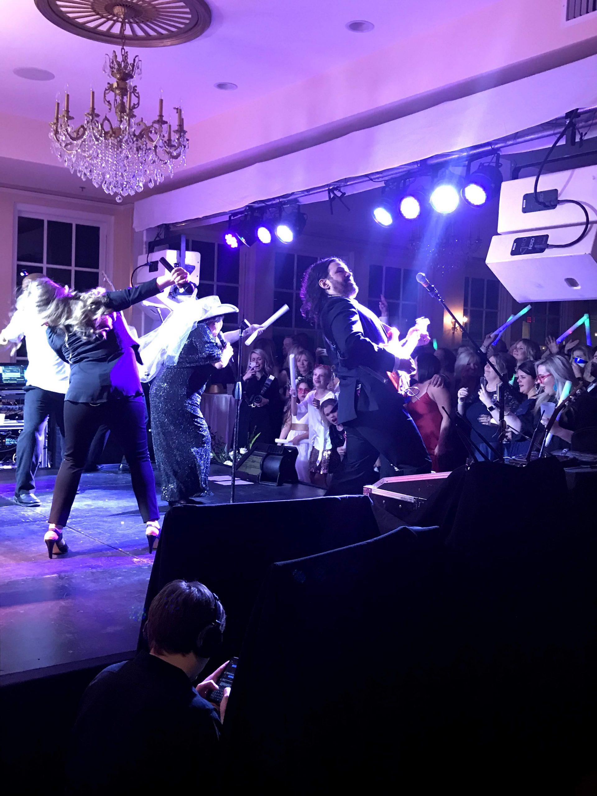 A high energy band performs on a stage prepared in the Bullock Ballroom.