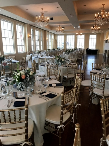 Round tables are covered in white linens and dark navy blue napkins. The centerpieces consist of mixed florals and tea lights.