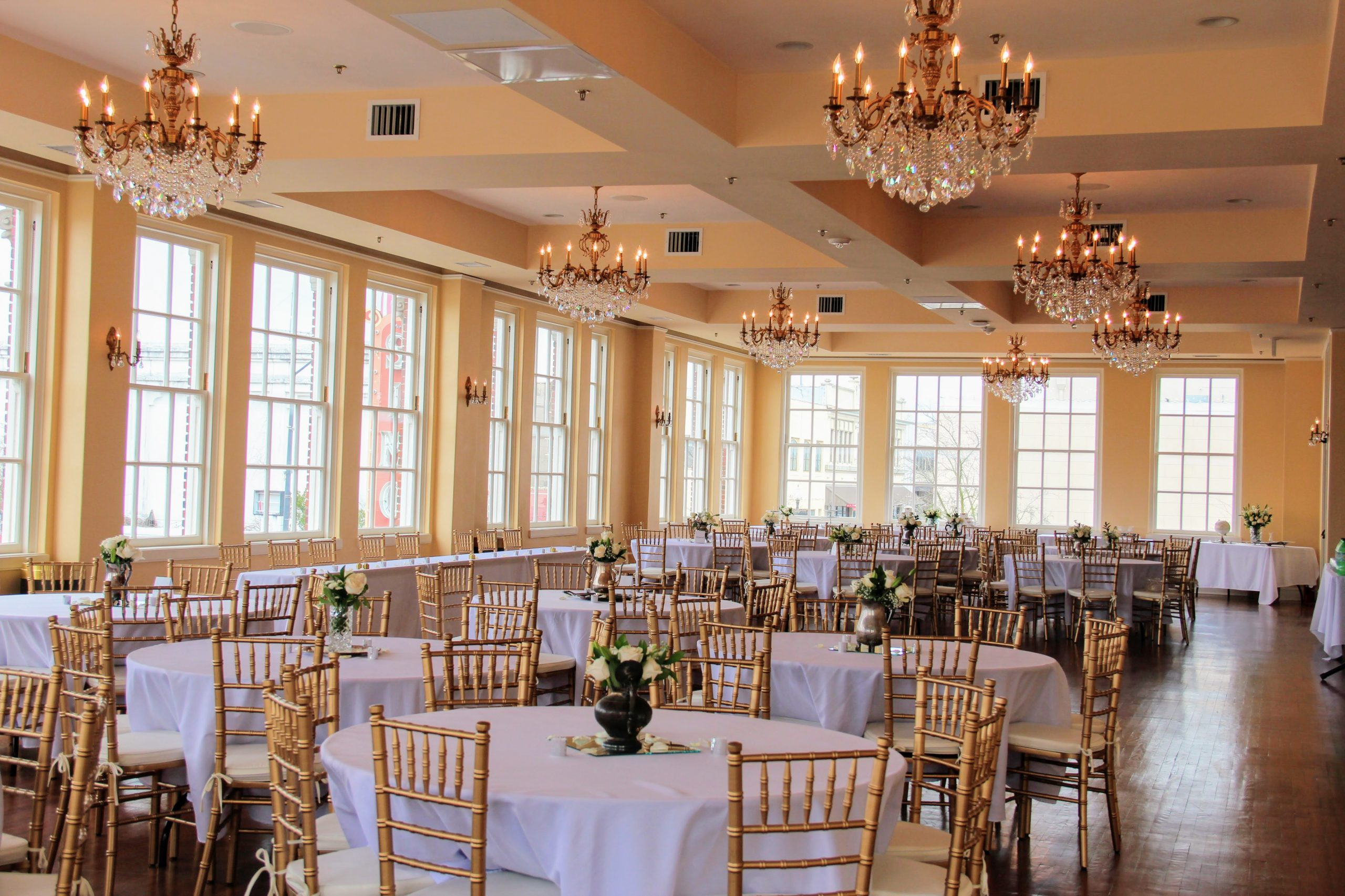 Silver teapots full of white roses and baby's breath sits atop glass mirrors sprinkled with rose petals and silver candles on white tables in the Bullock Ballroom.