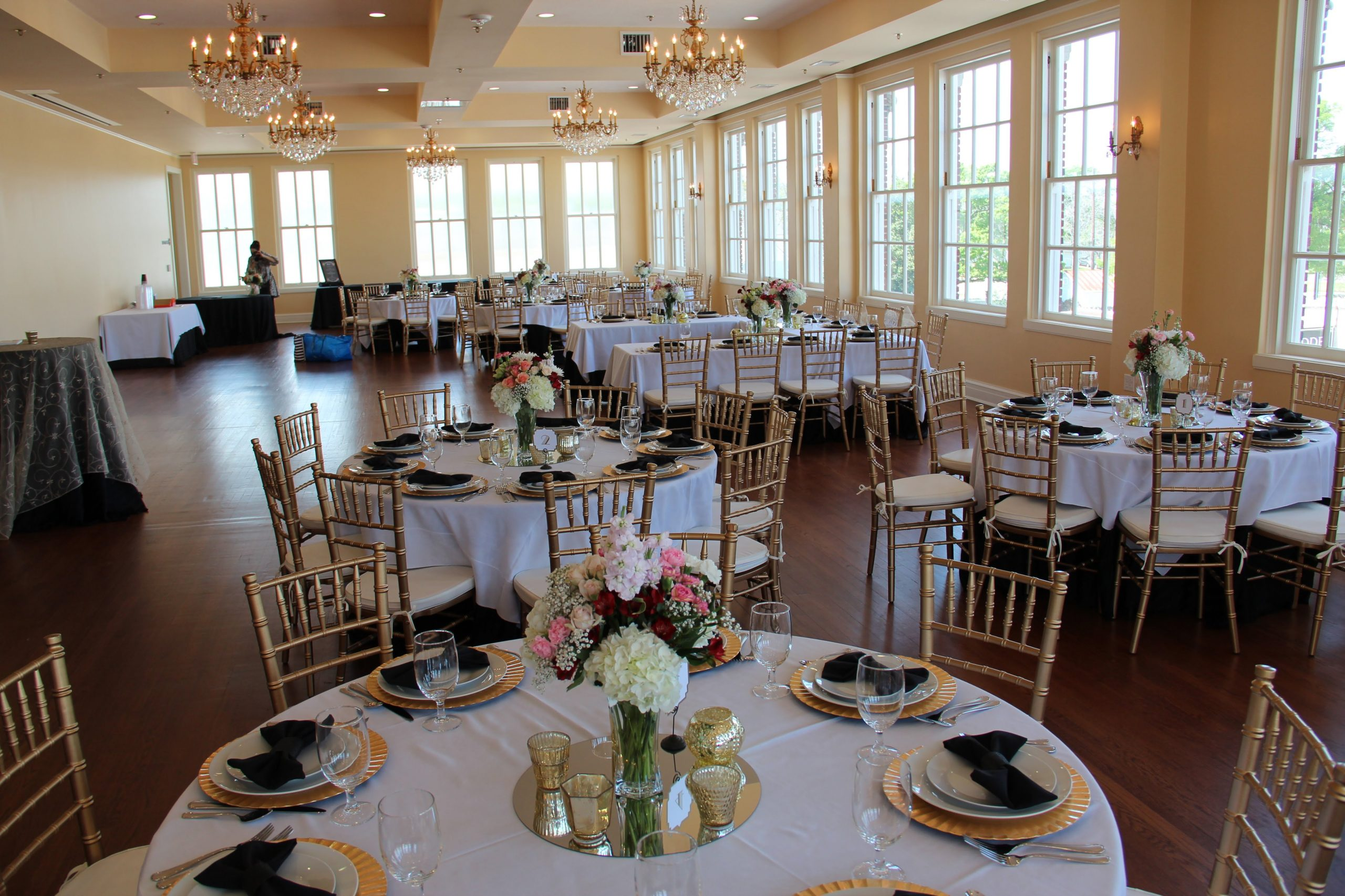 White linen tables decorated with gold charges, white china and black linen napkins. Centerpieces consist of glass mirror base, various candle holders, and a floral arrangement of mixed flowers.