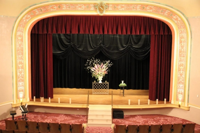 A vintage theatre with a stage set for a wedding with a large floral arrangement in the center and candles rimming the edge of the stage and aisle.