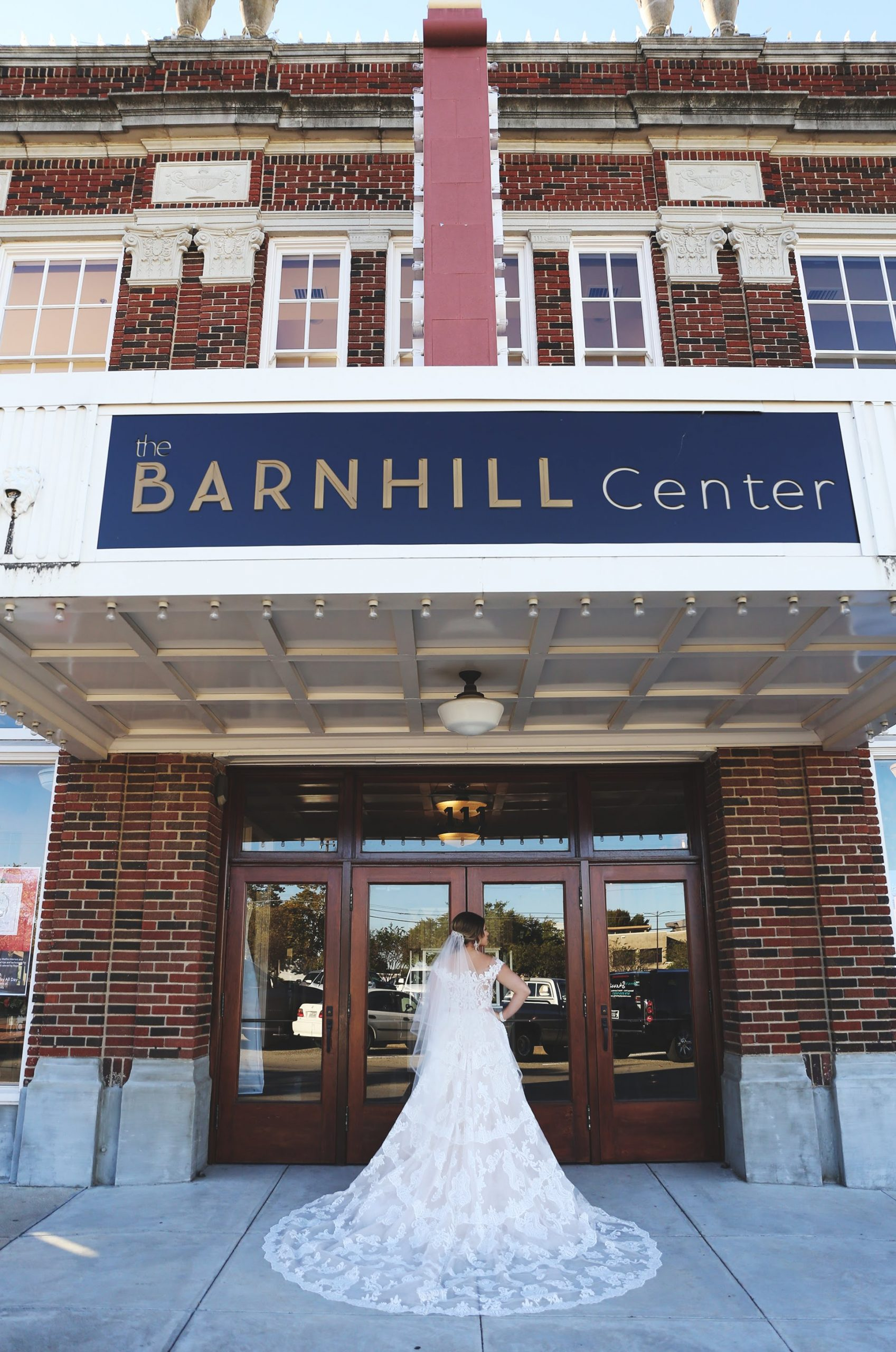 A bride in a white wedding dress stands underneath the exterior awning of The Barnhill Center entryway.