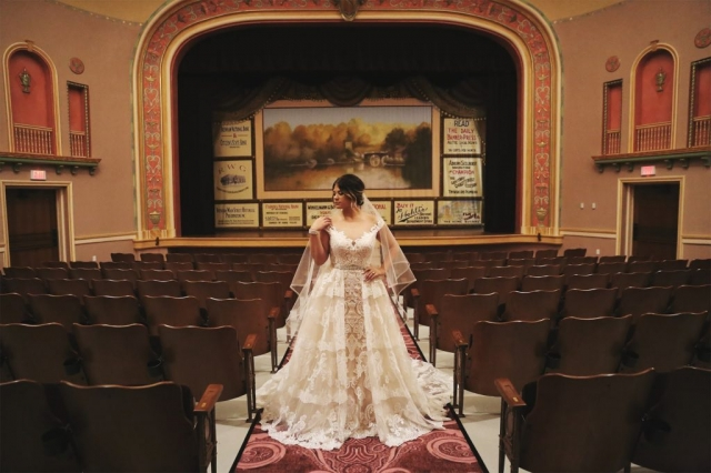 A bride in a white wedding dress stands in the aisle of a vintage Vaudeville theatre.