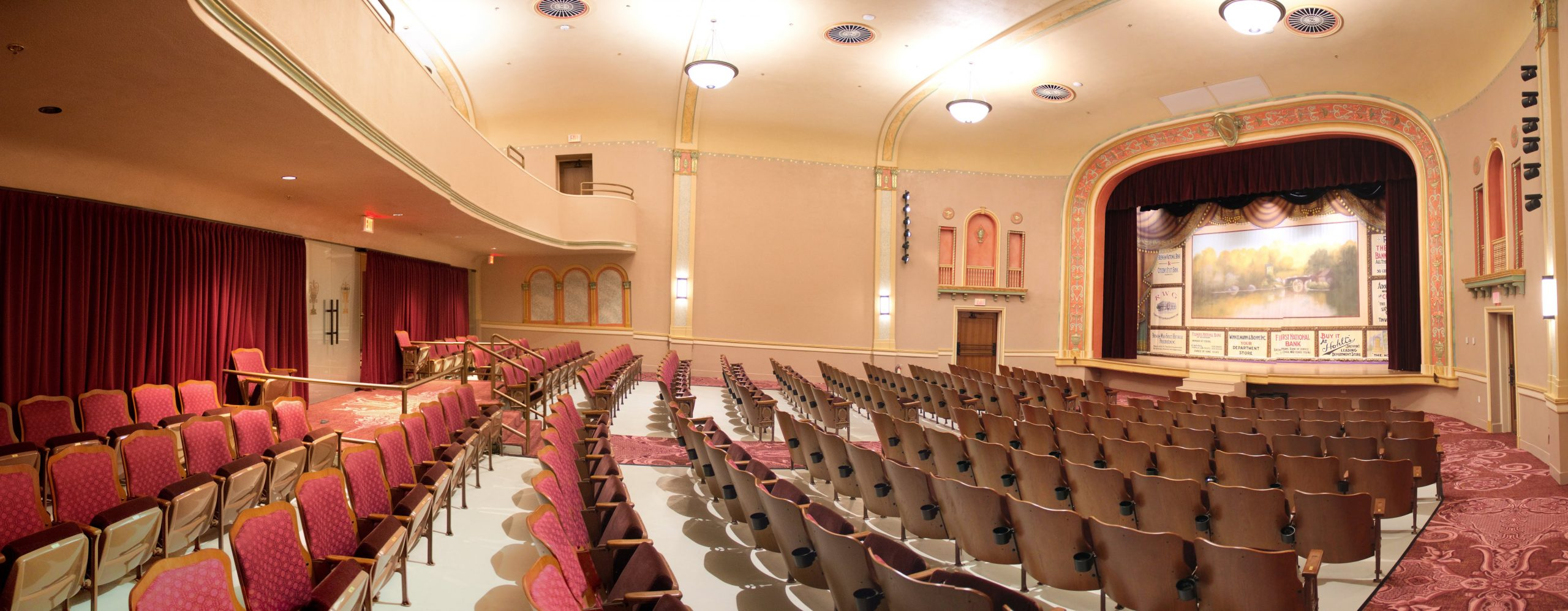 The historic Hasskarl Auditorium with rows of chairs facing a vintage stage with painted backdrop.