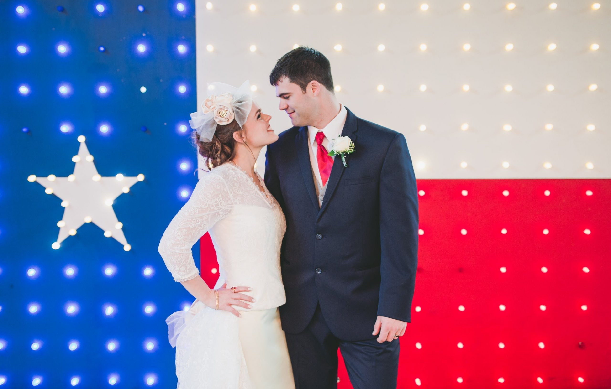 A bride and groom stand in front of an illuminated Texas flag.