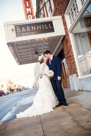 A bride and groom kiss outside of The Barnhill Center main doors as the Simon marquee glitters in the background.