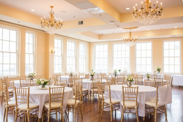 Round tables dressed in white linen are circled by gold Chiavari chairs. Tables are decorated with vintage teapots and white roses.