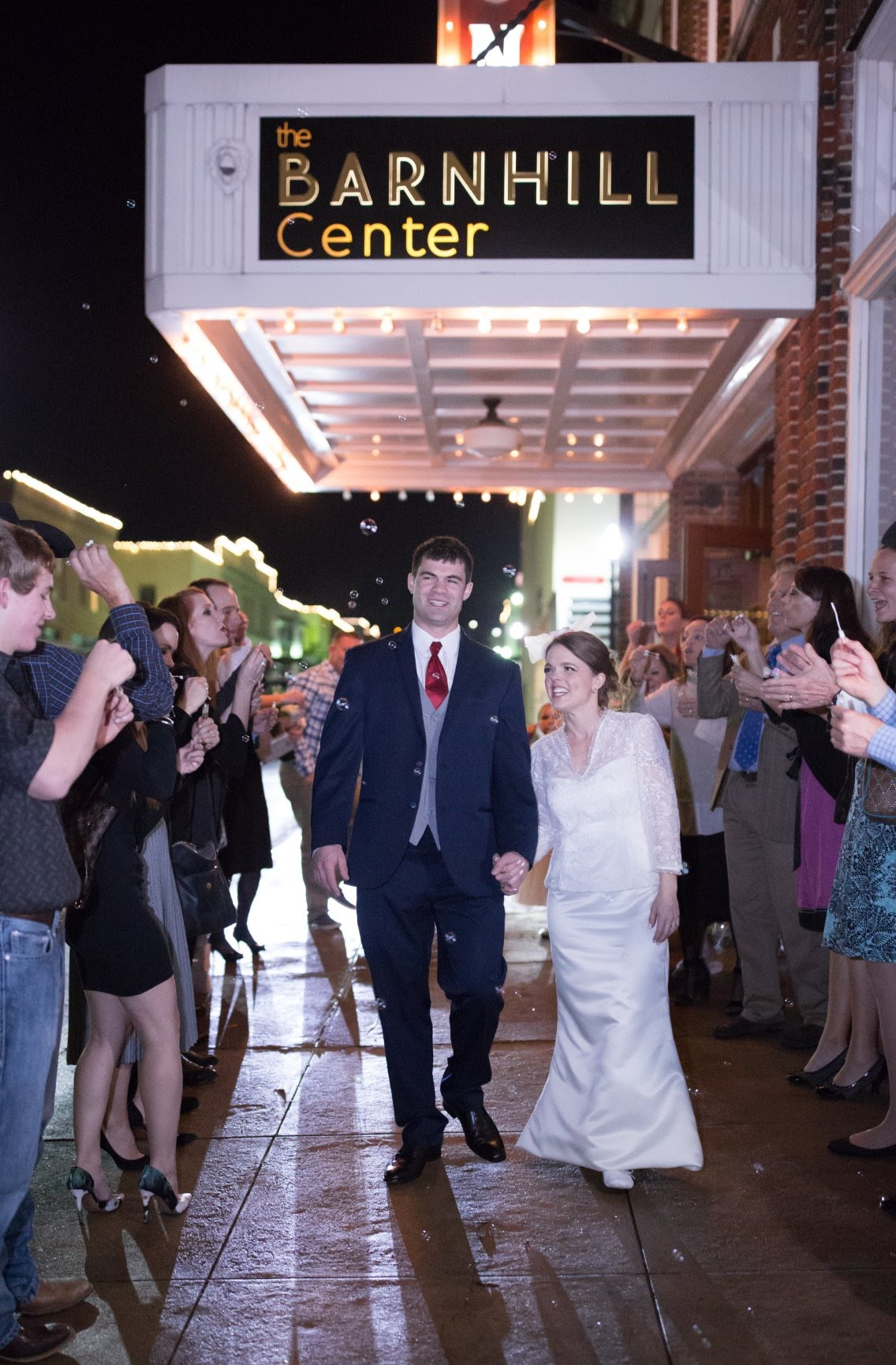 A happily married couple depart their wedding reception at The Barnhill Center as guests line the sidewalk outside and wish them well.