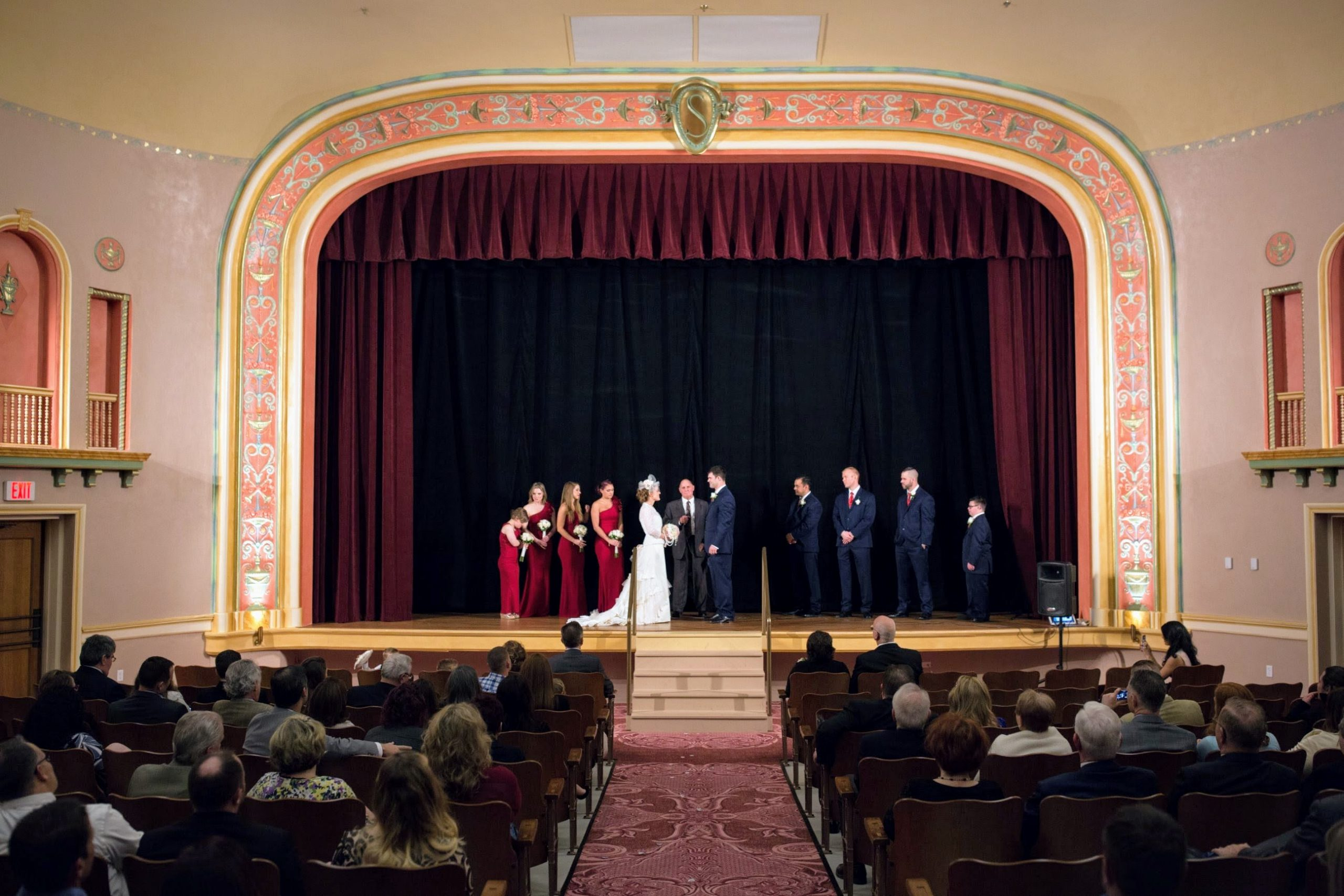 A wedding party is on stage of our vintage Vaudeville stage with groomsmen and bridesmaids flanking each side. Guests are seated below in the auditoriums roomy seats; watching the ceremony.